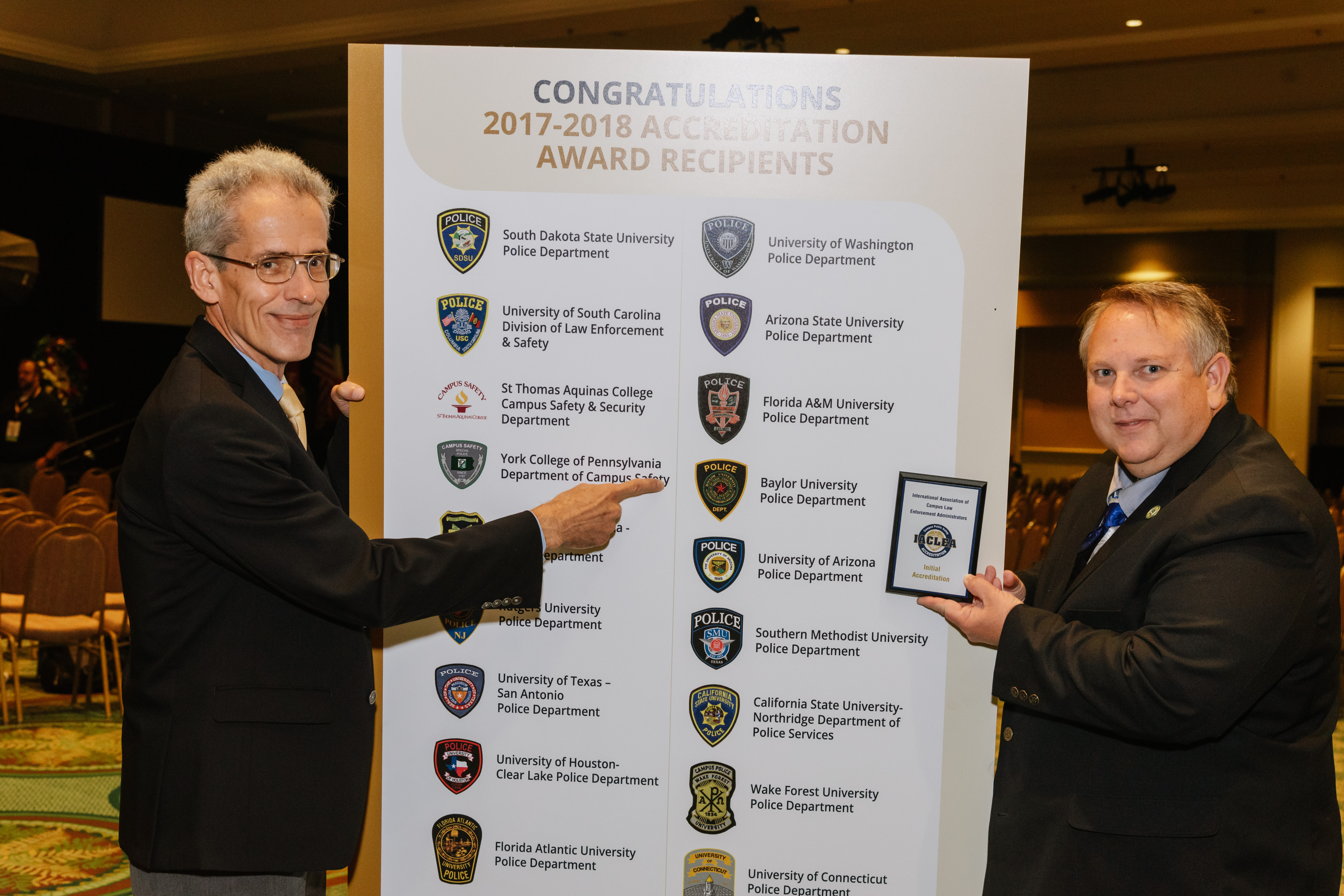 Baylor University Chief of Police Brad Wigtil and Accreditation Manager Sgt. Andrew Huntington point out their achievement following the Awards Ceremony at the 2018 Annual Conference & Exposition. © Mike Ritter